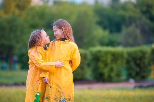 Adorables petites filles sous la pluie par une chaude journée d'automne