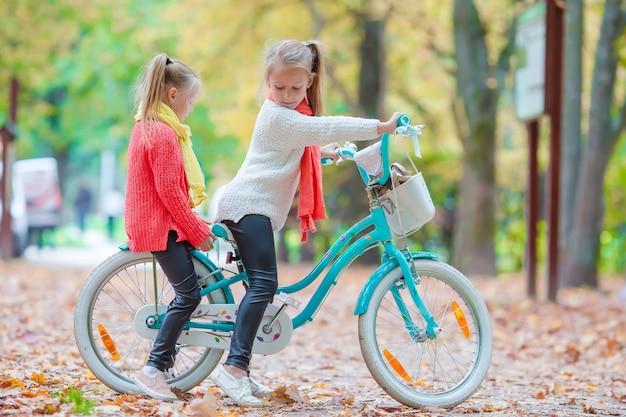 Adorables petites filles à vélo à la belle journée d'automne en plein air