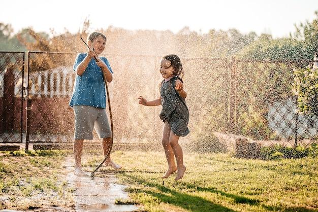 Adorables petits enfants jouant avec un tuyau d'arrosage par une chaude et ensoleillée journée d'été au coucher du soleil