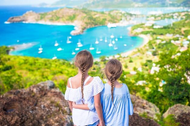 Adorables petits enfants profitant de la vue du pittoresque english harbour à antigua dans la mer des caraïbes