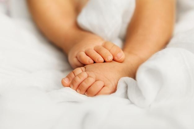 Adorables petits pieds de bébé sur blanc après le sommeil du matin, gros plan des orteils du nourrisson