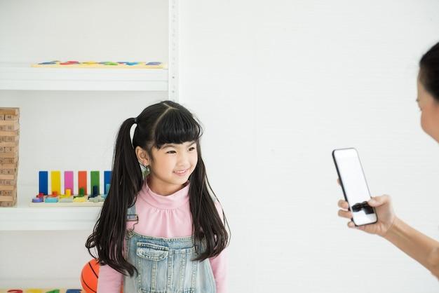 Adorbale fille sourire regarder le téléphone de la mère à la maison.