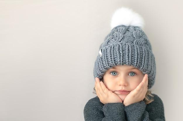 Adorible enfant fille aux grands yeux bleus en pull en laine grise et bonnet à pompon blanc regarde la caméra avec les mains sur les joues