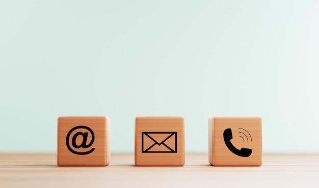 L'adresse e-mail, le numéro de téléphone et les icônes de lettre impriment l'écran sur un bloc de cube en bois sur une table pour le contact commercial de la page web et le concept de service client par rendu 3d.