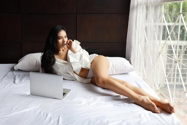 Adulte asiatique sexy femme vêtue d'une robe blanche, achats en ligne sur ordinateur avec carte de crédit en position couchée sur le lit dans la chambre