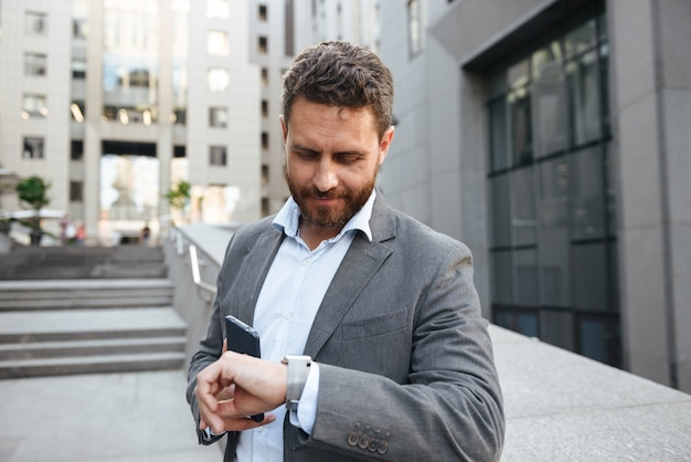 Adulte bel homme en costume gris tenant un téléphone mobile, et regardant la montre-bracelet en se tenant debout devant un immeuble de bureaux moderne