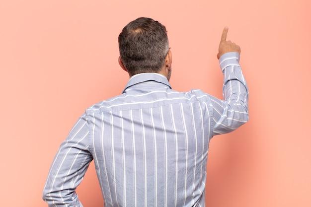 Adulte bel homme debout et pointant vers l'objet sur l'espace de copie, vue arrière