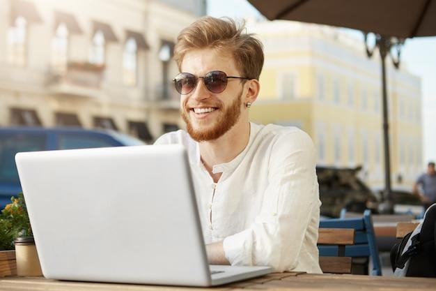 Adulte bel homme gingembre avec ordinateur portable assis sur la terrasse d'un restaurant ou d'un café