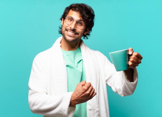 Adulte bel homme indien portant un peignoir et prendre un café