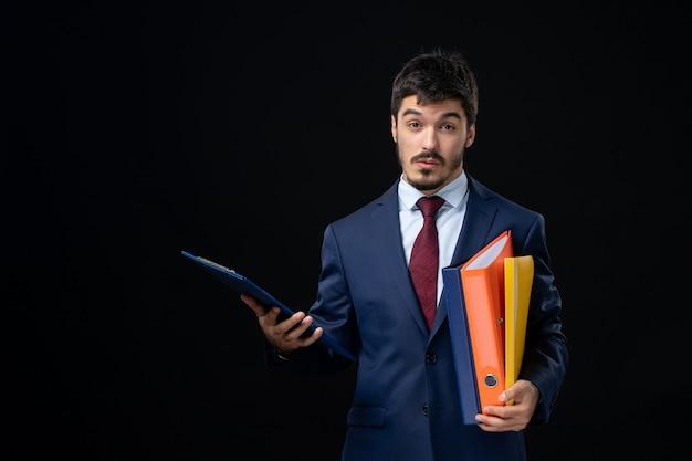 Adulte émotionnel surpris en costume tenant plusieurs documents sur un mur sombre isolé