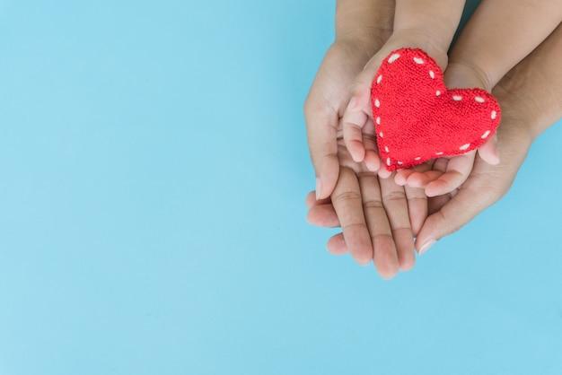 Adulte et enfant tenant un coeur rouge dans les mains, relations familiales heureuses