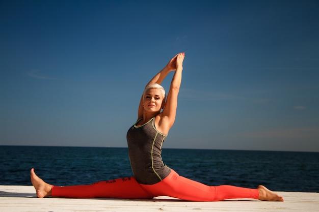 Adulte, femme blonde avec une coupe de cheveux courte, pratique le yoga sur la jetée dans le contexte de la mer et du ciel bleu