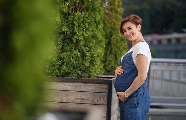 Adulte femme enceinte pose dans la nature parmi les arbres dans le parc
