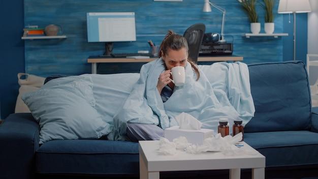 L'adulte frissonne et a froid en utilisant une couverture
