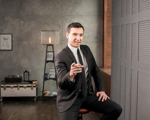 Adulte heureux homme d'affaires pointant à la caméra