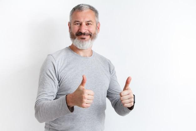 Adulte heureux homme aux cheveux gris avec une barbe montrant les pouces vers le haut sur blanc