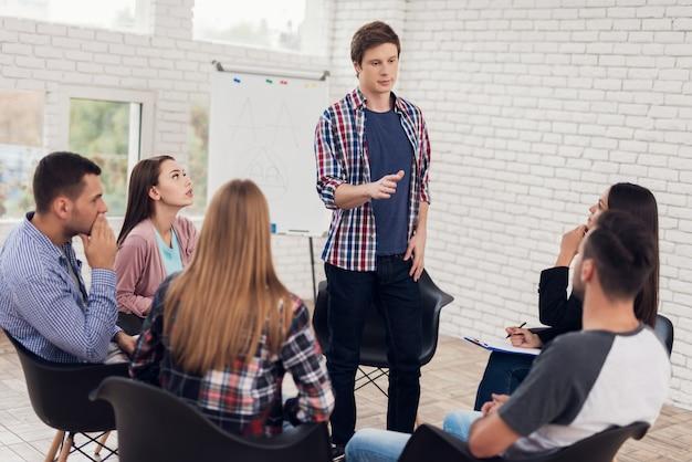 Adulte homme confiant en chemise à carreaux se dresse en cercle de personnes.