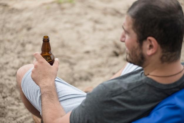 Adulte mec se reposant sur la plage avec de la bière