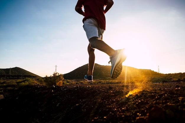 Un adulte qui court avec des vêtements de jogging seul dans les montagnes au coucher du soleil - fitness adolescent faisant de l'exercice isolé