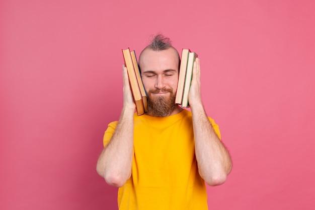 Adulte souriant gars vêtements décontractés avec barbe embrasse les livres préférés à lui-même isolé sur rose