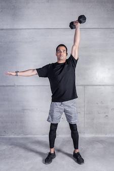 Adulte sportif avec haltère à la main au-dessus de la tête
