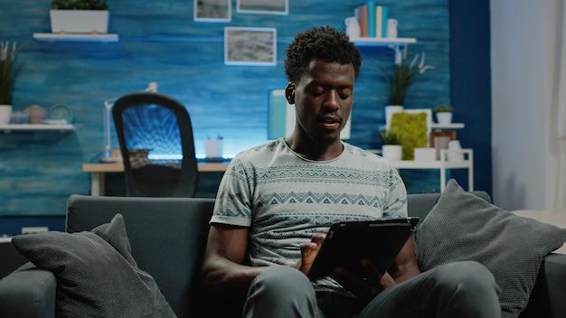 Adulte tenant une tablette numérique et tapant sur un écran tactile