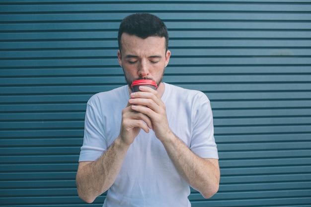 L'adulte tient une tasse de café près de la bouche. il garde les yeux fermés. isolé sur rayé