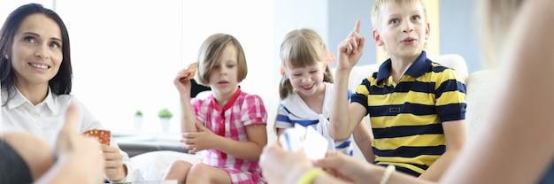 Adultes et enfants jouent ensemble à des jeux de société à la maison.
