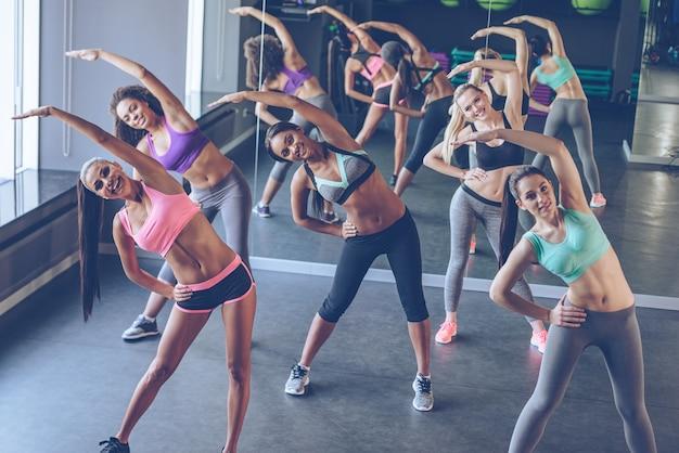 Aérobic avec des filles. jeunes belles femmes gaies avec des corps parfaits en vêtements de sport faisant de l'exercice et regardant la caméra avec le sourire au gymnase
