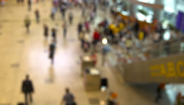 Aéroport. des gens flous dans le hall principal sont fermés pour voler le bureau annoncé.