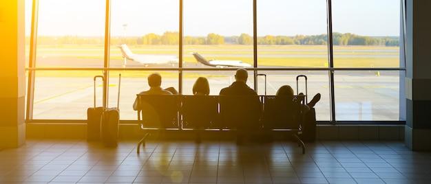 Aéroport de katowice, pologne - octobre 2018 : touristes assis dans l'aéroport avec des valises. les gens attendent le vol. photo de concept de voyage. avion en retard.