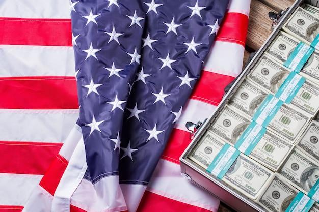 Affaire avec des liasses de dollars. drapeau américain posé à côté de l'argent. prospérité des affaires. la liberté financière telle qu'elle est.