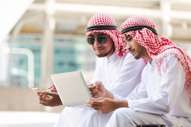 Affaires arabes assis travaillant dans la ville