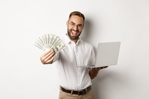 Affaires et commerce électronique. heureux homme d'affaires prospère se vanter d'argent, travaillant sur un ordinateur portable en ligne, debout sur fond blanc.