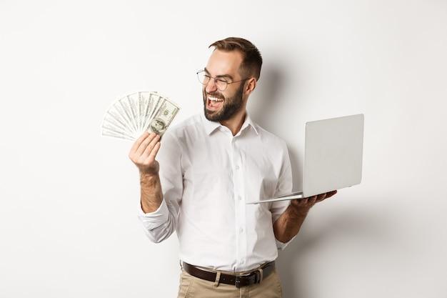 Affaires et commerce électronique. homme d'affaires prospère utilisant un ordinateur portable pour travailler et détenir de l'argent, debout sur fond blanc.
