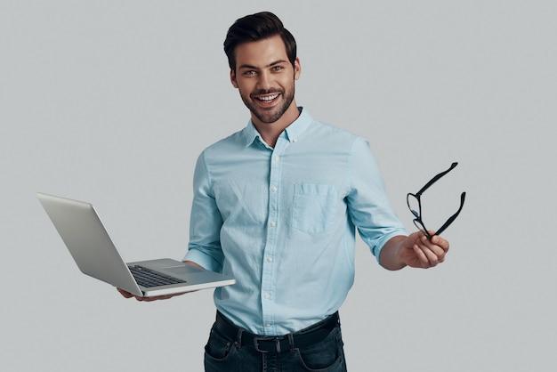 Les affaires, c'est sa vie. beau jeune homme utilisant un ordinateur portable et regardant la caméra avec le sourire en se tenant debout sur fond gris