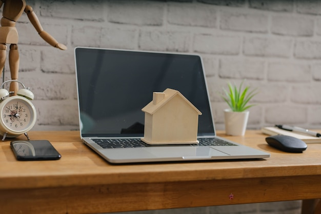 Affaires, finance, épargne, échelle de propriété ou concept de prêt hypothécaire, modèle de maison en bois sur ordinateur portable