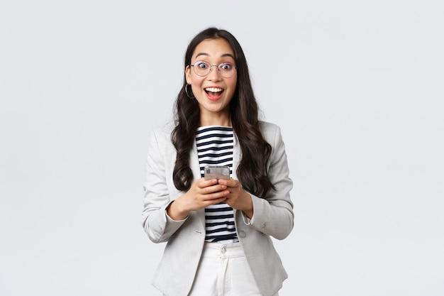 Affaires, finances et emploi, concept féminin d'entrepreneurs prospères. femme d'affaires asiatique joyeuse et heureuse, chef de bureau regardant une caméra optimiste avec le sourire, utilisant un smartphone