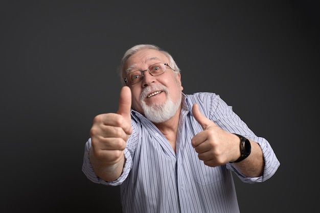 Affaires, homme grisonnant dans des verres sourit et montre son approbation
