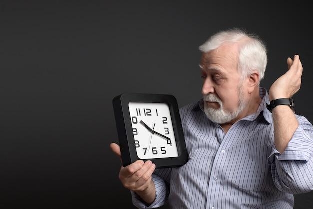 Affaires, homme grisonnant tenant une horloge murale. le temps presse