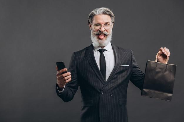 Affaires et homme mature barbu à la mode dans un costume gris avec emballage noir faisant du shopping et montrant la langue.