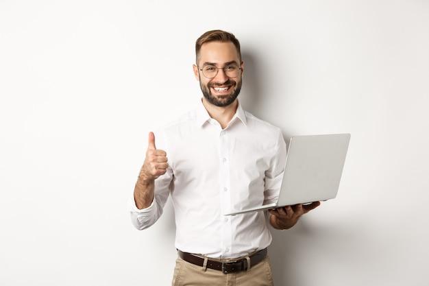 Affaires. jeune entrepreneur masculin prospère montrant le pouce vers le haut tout en travaillant sur un ordinateur portable, debout