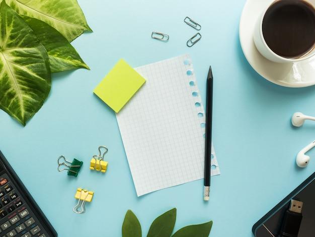 Affaires plat poser avec espace copie, calculatrice, crayon, bloc-notes, verres à café sur fond bleu coloré