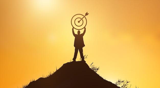 Affaires et succès, concept de personnes de réussite. silhouette d'homme d'affaires au sommet de la montagne sur la photo de fond de ciel coucher de soleil
