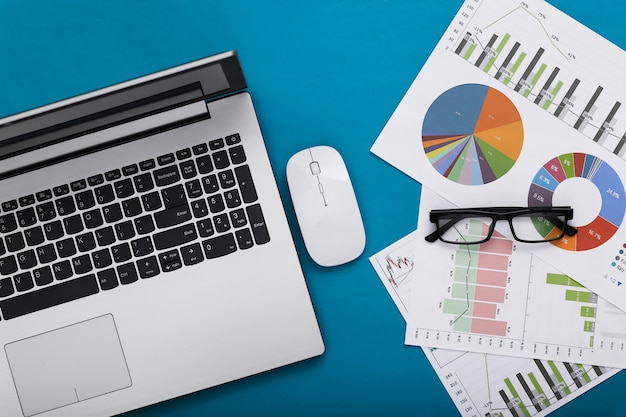 Affaires, sujet d'analyse économique. espace de travail d'économiste sur fond bleu. ordinateur portable, graphiques et tableaux avec lunettes. vue de dessus