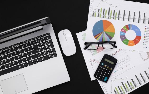 Affaires, sujet d'analyse économique. espace de travail d'économiste sur fond noir. ordinateur portable, graphiques et tableaux avec une calculatrice. vue de dessus