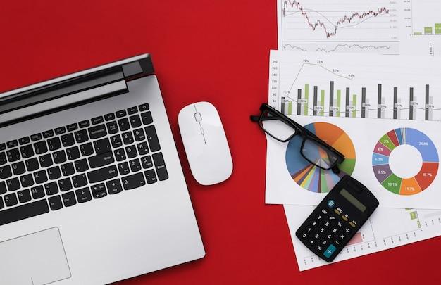 Affaires, sujet d'analyse économique. espace de travail d'économiste sur fond rouge. ordinateur portable, graphiques et tableaux avec une calculatrice. vue de dessus