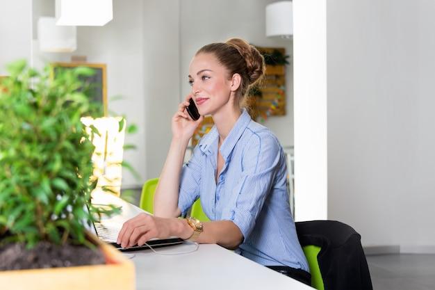 Affaires, technologie et concept de bureau vert - jeune femme d'affaires prospère avec ordinateur portable parlant au téléphone au bureau. belle femme à l'aide de la tablette tactile.