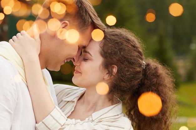 Affectueux jeune couple dansant sous les lumières lors d'une fête en plein air