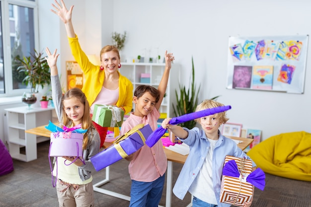 Affichage des boîtes présentes. trois élèves et un professeur joyeux montrant des boîtes à cadeaux incroyables après la décoration